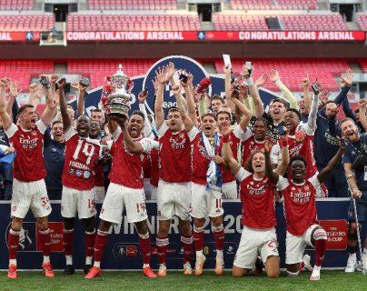 Los jugadores del Arsenal festejan con la Copa de campeones, después de vencer al Chelsea. Foto AFP.