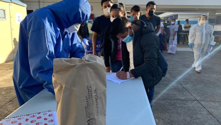 Migrantes reciben refacciones al salir del albergue Ramiro de León al finalizar su cuarentena. (Foto: Conamigua)