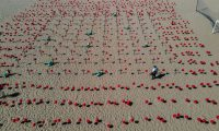 Con mil globos rojos en las arenas de la playa y cien de ellos fijados en cien cruces negras se rindió homenaje a los 100 mil brasileños fallecidos por la pandemia de coronavirus y se manifestaron en contra de la forma en que el Gobierno ha gestionado la crisis sanitaria. (Foto Prensa Libre: EFE)