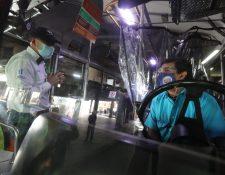 Edwin Asturias, director de Coprecovid conversó con un piloto de transporte durante el ensayo de protocolos del Transmetro y transporte extraurbano. (Foto Prensa Libre: Érick Ávila)