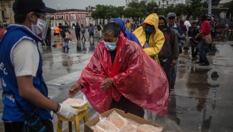 Un hombre recibe un almuerzo gratuito en la Plaza de la Constitución este 10 de septiembre por parte del proyecto La Olla Comunitaria, quienes han colaborado durante la crisis del coronavirus. Fotografía: Prensa Libre.