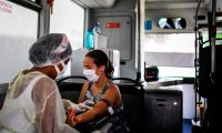 A nurse prepares to take a blood sample from a woman for a coronavirus test inside a bus converted into a test lab at the Sao Domingos de Rana high school in Cascais on September 14, 2020. - A coronavirus bus travelled through several schools in Cascais in the outskirts of Lisbon to deliver free COVID-19 tests to teachers and school employees days before the beginning of the academic year. (Photo by PATRICIA DE MELO MOREIRA / AFP)