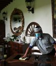 Un empleado limpia una mesa en el área de restaurante de un hotel en Antigua Guatemala que comenzó la reapertura en medio de la pandemia. (Foto Prensa Libre: AFP)