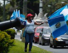 Lucía López camina en la avenida la Reforma, zona 10; vendiendo banderas durnate ocho horas al día. (Foto Prensa Libre: Esbin García)