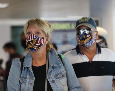 Una pareja utiliza mascarillas para protegerse del coronavirus mientras esperan para abordar un avión en un aeropuerto de Estados Unidos. (Foto: Hemeroteca PL)