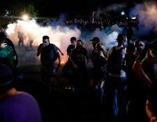 Agentes policiales de Kenosha, Wisconsin, lanzan gases lacrimógenos para contener a los manifestantes. (Foto Prensa Libre: AFP)