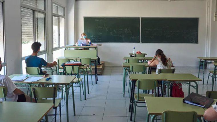 Aula con profesora y alumnos con mascarilla y una persona por cada par de pupitres. Shutterstock / F. Altamirano