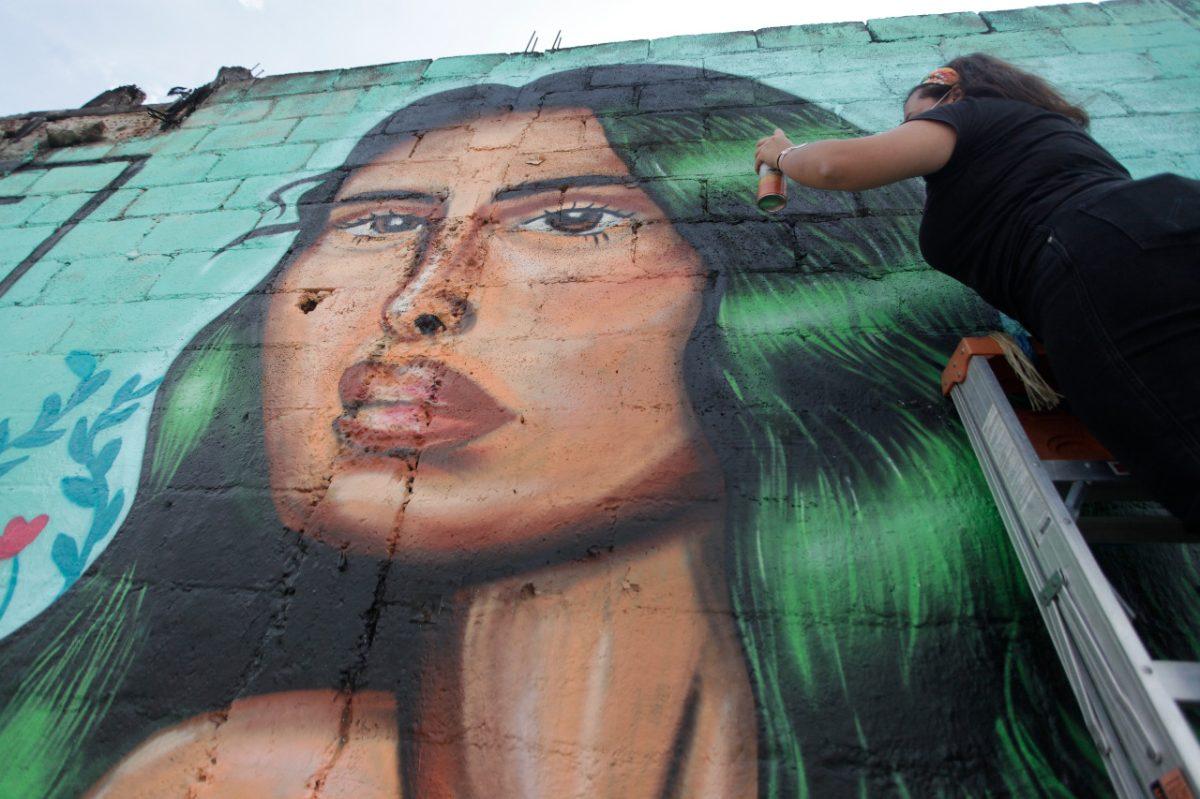 Artista pinta mural en el marco del festival Cuerpos Libres