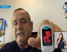 Alejandro Giammattei muestra un oxímetro con el registro de 95% de pulso y 97% de saturación.