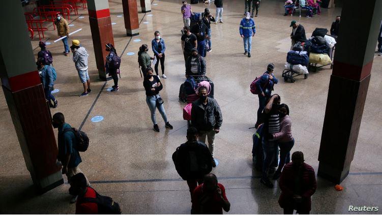 Pasajeros con mascarillas protectoras hacen fila en la boletería de la terminal de transporte, en medio del brote de la enfermedad por coronavirus (COVID-19), en Bogotá.