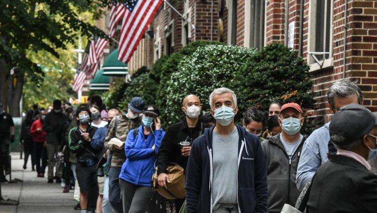 La gente espera en una fila para votar en la Biblioteca Pública de Queens durante la votación anticipada para las elecciones presidenciales de los Estados Unidos el 24 de octubre de 2020. (Foto Prensa Libre: AFP)