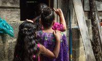 La hermana pequeña de Marta la abraza durante la celebración de su cumpleaños 15 en una aldea de Cobán, el 5 de octubre de 2020, en Cobán. Marta es una de las 22 niñas que acusan a maestros y trabajadores del ministerio de educación de Guatemala por violaciones sexuales. (Foto Prensa Libre: EFE)