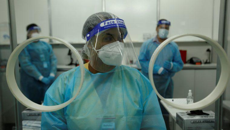 Personal médico privado realiza pruebas de hisopados para detectar covid-19. (Foto Prensa Libre: AFP)