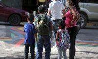 AME2449. TEGUCIGALPA (HONDURAS), 19/10/2020.- Una madre con sus hijos espera un bus urbano hoy en Tegucigalpa (Honduras). Miles de niños hondureños se han visto obligados a salir a la calle, abandonar el sistema educativo y se enfrentan al hambre, discriminación y al trabajo infantil por la crisis desatada por la pandemia de la covid-19 en su país. EFE/Gustavo Amador