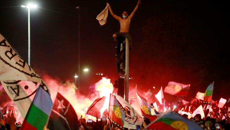 Decenas de personas celebran luego de conocer los resultados parciales del plebiscito constitucional, que apuntan al triunfo por una nueva Carta Magna hoy, en Santiago (Chile). Foto Prensa Libre: EFE.