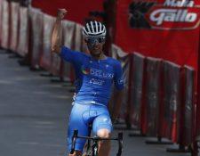 El guatemalteco, Julio Padilla, de Ópticas Deluxe, levanta el brazo derecho en señal de triunfo. El ciclista brilló este viernes en la primera etapa de la vuelta al país. Foto: Esbin García.