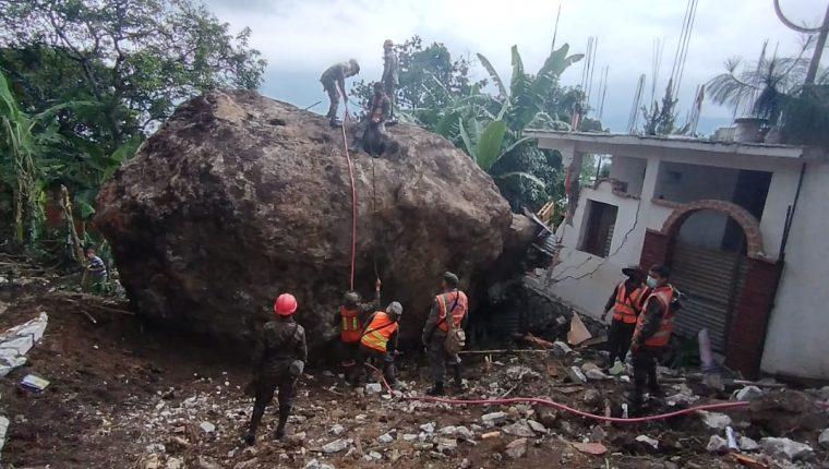 Personal de la Conred y del Ejército de Guatemala trabajan para retirar la enorme roca que cayó en viviendas de San Marcos La Laguna, Sololá. (Foto Prensa Libre: Conred)