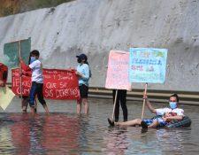 Con carteles, flotadores y pelotas de playa, jóvenes manifiestan contra corrupción en la obra del Libramiento de Chimaltenango que tiene tramos inundados. (Foto, Prensa Libre: Juan Diego González).