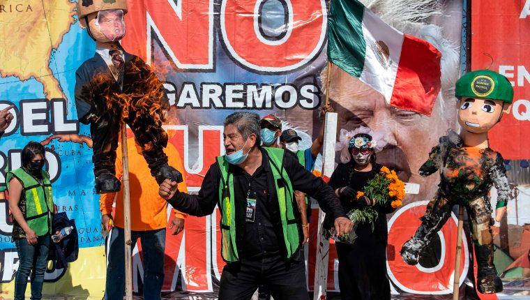 Los migrantes quemaron figuras del presidente de Estados Unidos, Donald Trump. (Foto Prensa Libre: AFP)