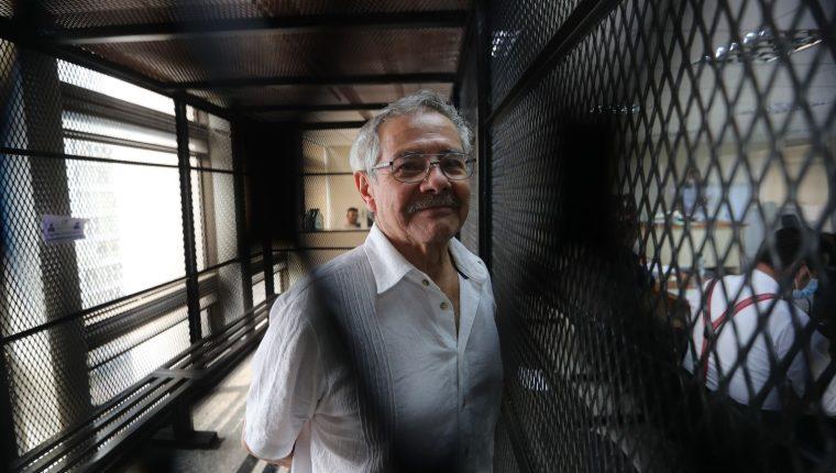 César Macías, alias César Montes, ve hacia las cámaras de fotoperiodistas en la carceleta del Juzgado de Mayor Riesgo E. (Foto Prensa Libre: Érick Ávila)
