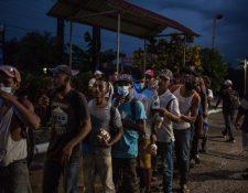 Migrantes hondureños esperan recibir alimentos de un grupo de voluntarios del albergue de migrantes de Esquipulas, Chiquimula. (Foto Prensa Libre: EFE)