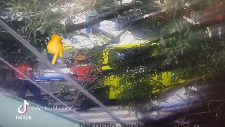 Imagen captada por una cámara de seguridad que muestra a los Bomberos Municipales mientras trasladan a la mujer herida. (Foto Prensa Libre: Amilcar Montejo)