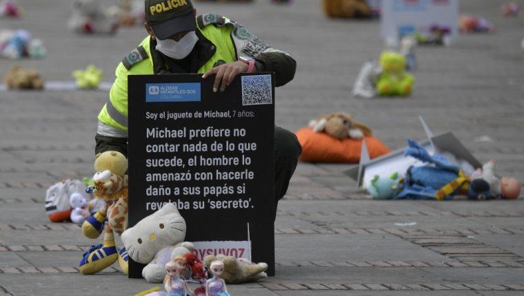 Un policía observa algunos de los peluches colocados como protesta en Colombia. (Foto: AFP)