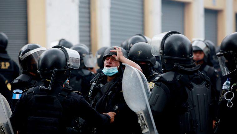Un agente de la policía afectado por gases lacrimógenos es atendido durante las protestas en contra del Gobierno del presidente Alejandro Giammattei el pasado 21 de noviembre. (Foto Prensa Libre: EFE)