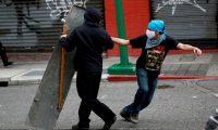 GRAF3316. CIUDAD DE GUATEMALA, 22/11/2020.- Los manifestantes arrojan piedras a la Policía durante los disturbios entre la policía y los manifestantes que ocuparon y prendieron fuego al Congreso en Ciudad de Guatemala este domingo tras las protestas en contra del Gobierno del presidente Alejandro Giammattei. Al menos 22 personas han sido detenidas durante los disturbios. EFE/ Esteban Biba