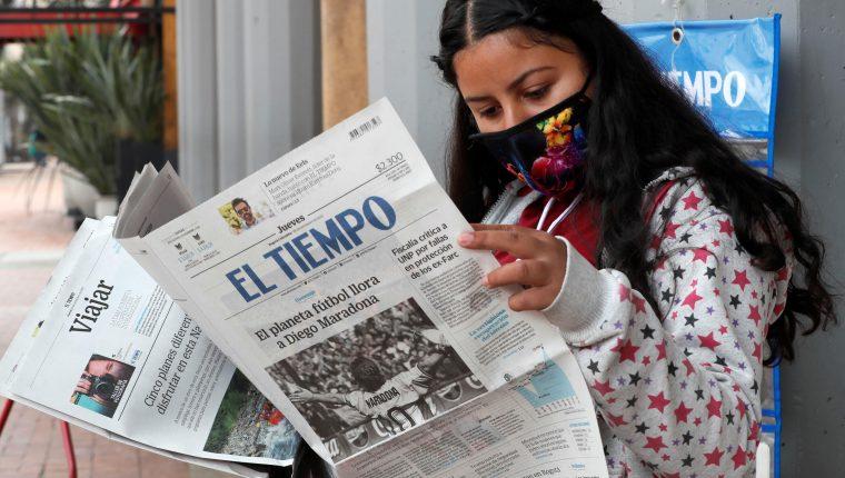 Una mujer lee el periódico El Tiempo, el cual registra en su portada el fallecimiento de Diego Armando Maradona. Foto Prensa Libre EFE.