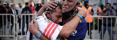 Un aficionado con la camiseta de Boca Juniors y otro con la de River Plate, se abrazan luego de despedir los restos de Diego Armando Maradona en el velatorio de la capital bonaerense, en la Plaza de Mayo. Foto Prensa Libre: EFE.