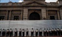 AME1774. CIUDAD DE GUATEMALA (GUATEMALA), 28/11/2020.- Policías montan guardia durante una protesta contra el Gobierno y el Congreso de la nación hoy, en Ciudad de Guatemala (Guatemala). Un grupo de manifestantes encapuchados quemó este sábado un autobús en la esquina del Palacio Nacional de la Cultura (oficina de Gobierno) de Guatemala, en medio de la protesta ciudadana pacífica que se desarrollaba en contra del Gobierno y Congreso. EFE/ Esteban Biba