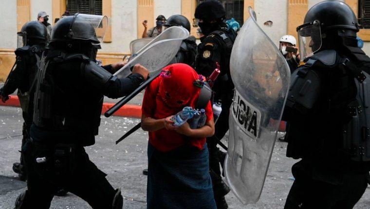 Policías golpean a una de las manifestantes que participó en las protestas contra el gobierno de Alejandro Giammattei y los diputados oficialistas que aprobaron el presupuesto nacional para 2021 (Foto Prensa Libre: AFP)