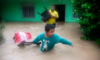 A boy and a man save chairs from a flooded house due to the heavy rains caused by Hurricane Eta, now degraded to a tropical storm, in Puerto Barrios, Izabal 310 km north Guatemala City on November 5, 2020. - At least four people, including two children, died in landslides as tropical storm Eta swept through Guatemala, civil protection officials said Thursday. The deaths brought the toll in Central America to eight after Eta tore into northern Nicaragua as a Category 4 hurricane on Tuesday causing mudslides that killed two miners, as well as two young girls in neighboring Honduras. (Photo by Johan ORDONEZ / AFP)