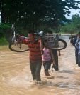 Personas tratan de ponerse a salvo en una comunidad de Panzós, Alta Verapaz. (Foto Prensa Libre: AFP)