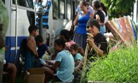 """People prepare to be evacuated from banana fields onboard a minibus in La Lima municipality, Cortes department, Honduras, ahead of the arrival of Hurricane Iota on November 15, 2020. - Hurricane Iota is forecast to strengthen to an """"extremely dangerous"""" Category Four by the time it makes landfall in Central America on Monday, the US National Hurricane Center warned, two weeks after powerful storm Eta devastated much of the region and left more than 200 people dead or missing. (Photo by Orlando SIERRA / AFP)"""