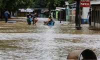 """People stay on a flooded street due to the overflow of the Chamelecon river in La Lima municipality, Cortes department, northern Honduras, on November 18, 2020, following the passage of Hurricane Iota, now degraded to a tropical storm. - Storm Iota, which made landfall in Nicaragua as a """"catastrophic"""" Category 5 hurricane Monday, killed at least ten people as it smashed homes, uprooted trees and swamped roads during its destructive advance across Central America. (Photo by Wendell ESCOTO / AFP)"""