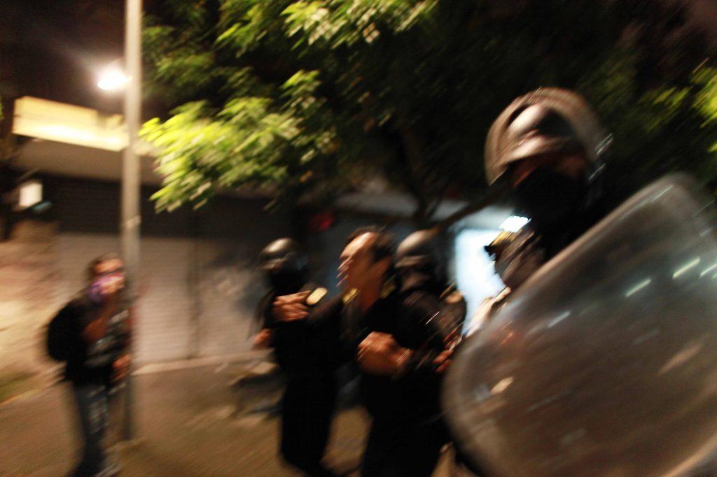 2. Un agente de la policía antimotines se acerca al fotoperiodista y quiere alejarlo del espacio.