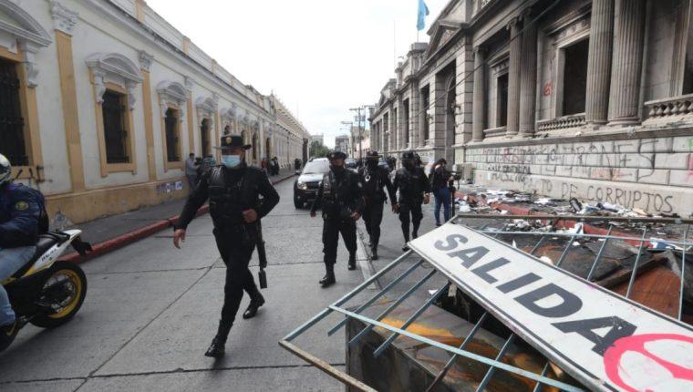 Policías avanzan frente al Congreso, en donde se pude observar parte de los daños causados en la protesta del 21 de noviembre.  (Foto Prensa Libre: Érick Ávila)