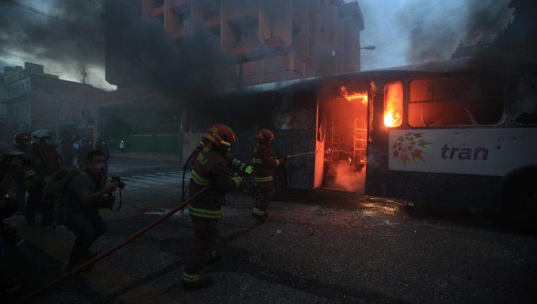 Encapuchados irrumpen la paz de la manifestación del 28 de noviembre, queman un bus y agreden a agentes de la PNC. Fotografía. Prensa Libre (Carlos Hernández).