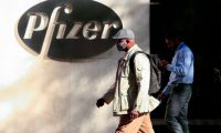 """TOPSHOT - People walk by the Pfizer world headquarters in New York on November 9, 2020. - Pfizer stock surged higher on November 9, 2020 prior to the opening of Wall Street trading after the company announced its vaccine is """"90 percent effective"""" against Covid-19 infections. The news cheered markets worldwide, especially as coronavirus cases are spiking, forcing millions of people back into lockdown. (Photo by Kena Betancur / AFP)"""