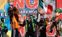 """A demonstrator cheers as pinatas depicting US President Donald Trump (L) and a US border patrol agent (R) are burnt during a protest against Trump's migration policies, next to banners hanging from the border fence, in Playas de Tijuana, Baja California state, on the border with the US, on October 31, 2020 - Trump said in an interview with Mexican newspaper El Universal released Friday, that he will keep hard migration policies with Mexico if he wins the election, and that he presumes there will be a good relationship with the country, since he """"wants to make America great again, and President Lopez Obrador wants to make Mexico great again"""". (Photo by Guillermo Arias / AFP)"""