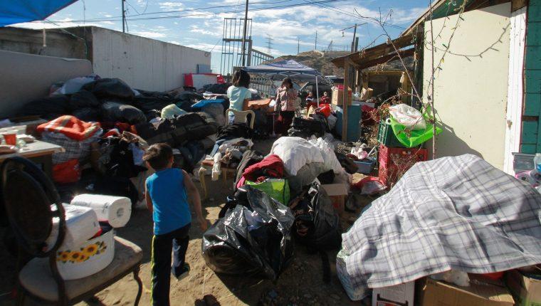 Migrantes centroamericanos que residen en un albergue en la ciudad mexicana de Tijuana, llevan apoyo en especie a familias que perdieron sus hogares. (Foto Prensa Libre: EFE)