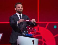 Daniele De Rossi sostiene el nombre de Italia durante el sorteo de la ronda de clasificación para el Mundial de Qatar 2021. Foto Prensa Libre: AFP