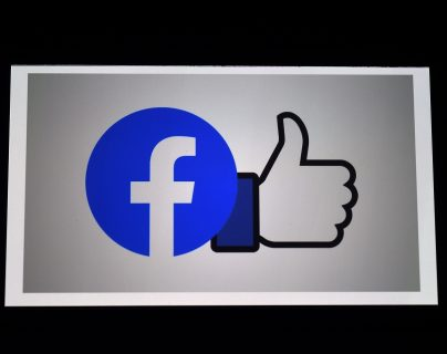 (FILES) In this photo illustration a Facebook App logo is displayed on a smartphone on March 25, 2020 in Arlington, Virginia. - Facebook confirmed on December 30, 2020 it was closing its Irish subsidiaries at the center of a dispute on profit shifting to avoid taxes in the United States. (Photo by Olivier DOULIERY / AFP)