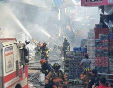 Los Bomberos Voluntarios y Bomberos Municipales Departamentales trabajan en conjunto para apagar el incendio en la Terminal Minerva. (Foto Prensa Libre: CBMD)