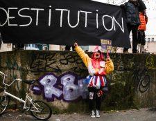Un manifestante disfrazado de payaso junto a un cartel que dice 'despido' en una protesta contra la controvertida ley de seguridad global de Francia. (Foto Prensa Libre: EFE)