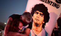 (FILES) In this file photo taken on November 25, 2020 a man and his daughter, fans of Argentinian football legend Diego Maradona, mourn as they gather by the Obelisk to pay homage on the day of his death in Buenos Aires. - Diego Maradona's death on November 25, 2020 shook the world of sport. The surprise and pain over the death of the football troubled genius at the age of 60 reinforced his myth and multiplied the tributes that seek to immortalize him. (Photo by RONALDO SCHEMIDT / AFP)