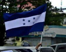 Un hombre sostiene la bandera nacional de Honduras mientras participa en una caravana por el Boulevard Morazán, el 15 de julio de 2020.