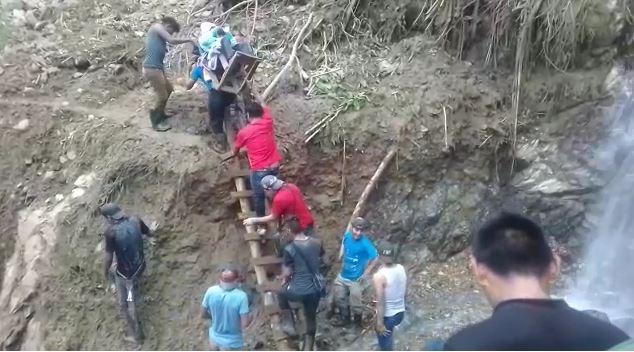 Personas ayudan a trasladar aun adulto mayor ante la falta de carreteras que comunican a la aldea Palo Grande, en Chiantla. (Foto Prensa Libre)